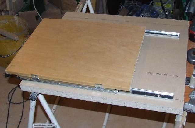 Another rectangle wood on the drawer slides over the base rectangle wood. where sliders allow left-right movement of it-